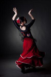 12377537 - young woman dancing flamenco on black