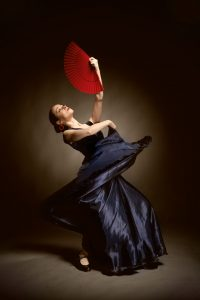 23878556 - young woman dancing flamenco on black