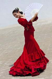 7167774 - woman traditional spanish flamenco dancer dancing in a red dress with a white fan