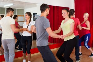 Happy men and women enjoying active dance at a dance studio