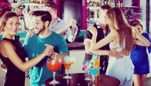 Young women with men are dancing in pairs оn the dance floor in the nightclub