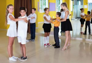 Group of diligent friendly children dancing tango in dance studio