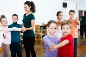 Group of children dancing pair dance in dance hall