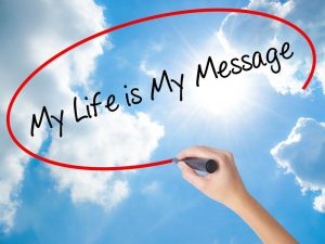 Woman Hand Writing My Life is My Message with black marker on visual screen. Isolated on Sunny Sky. Business concept. Stock Photo