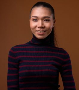 Studio shot of young beautiful Asian transgender woman against brown background