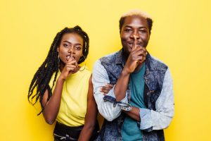 Portrait of a smiling young afro american couple showing silence gesture isolated over yellow