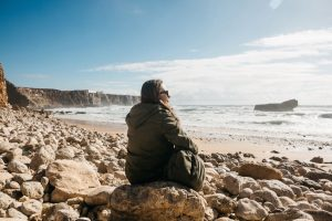 A girl with a backpack or a tourist or a traveler in solitude admires a beautiful view of the Atlantic Ocean in Portugal. Search for soul or unity with nature.