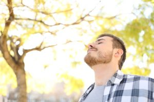 Relaxed man is breathing deep fresh air in a park with trees in the background