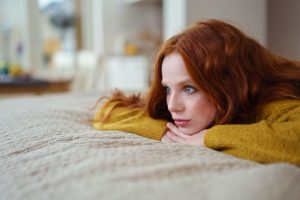 Attractive young redhead woman lying on her bed on her stomach thinking resting her chin on her hands and staring into the distance