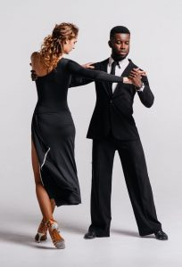 Couple dancers posing over white background. Man and woman are dancing. Colorful dance costumes. International dance group. Dancers dance. Passionate original variety of pair of dancers.
